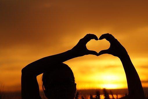 Doigts formant un coeur devant un coucher de soleil