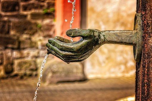 L'eau d'une fontaine coule dans une main sculptée en bronze