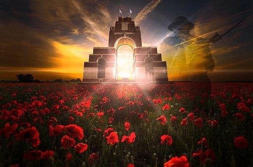 Coucher de soleil au travers d'un monument aux morts, devant un champ de Coquelicots