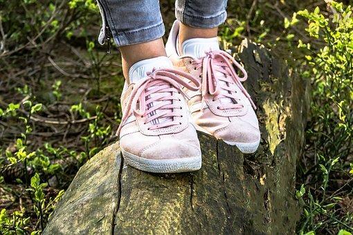Pieds d'enfant en baskets roses sur un tronc